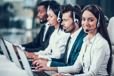 Photo for Multicultural young happy employees in call center sitting at computers and working. Teamwork. Employees in headset. - Royalty Free Image