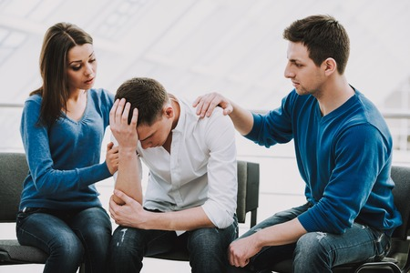 Foto de Feeling pain and depression. Depressed young man sitting at chair while two other people comforting his. - Imagen libre de derechos