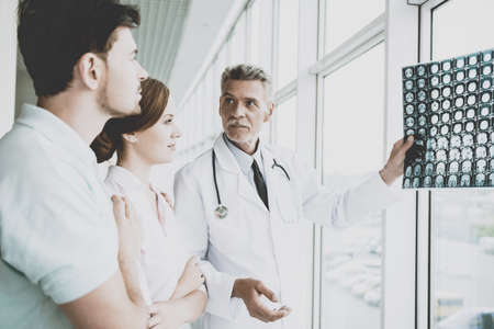 Foto de Tense Male Doctor Indicates on Image of Roentgen. Showing Patients Results at Diagnostic Centre. Rapid Improvement. Doctors and Patients Discuss in Clinic. Professional in Coat with Stethoscopes. - Imagen libre de derechos