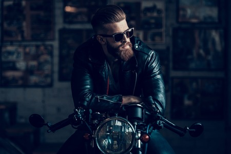 Photo pour Young Bearded Biker Sitting on Motorcycle in Garage. Indoor Garage. Young Mechanic in Garage. Parts of Motorcycle. Man in Checkered Shirt. Man on Vintage Bike. Biker Lifestyle Concept. - image libre de droit