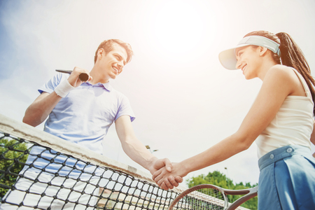 Photo pour Couple Shakes Hands with each other after Tennis Match Between them.Recreation Concept. Family Leisure. Caucasian Couple. Training Together. Practice Sport with Girlfriend. Athletic Couple. - image libre de droit