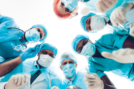 Foto de Doctors Staring On Patient. Operating Table Look. Preparing To Surgery. Clinician Team Group. Physician Assistants. Working Together. Teamwork Connection. Holding A Scalpel. Medicine In Masks. - Imagen libre de derechos