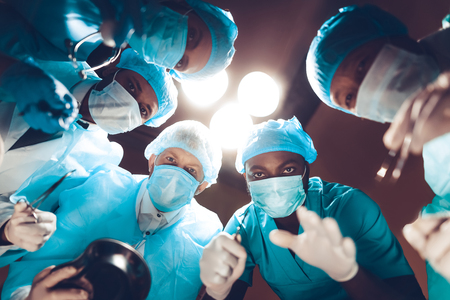 Foto de Doctors Staring On Patient. Operating Table Look. Preparing To Surgery. Clinician Team Group. Under The Light. Working Together. Teamwork Connection. Holding A Scalpel. Medicine In Masks. - Imagen libre de derechos