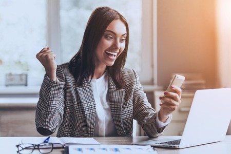 Photo for Young Handsome Lady Using Smartphone and Smiling while Sitting at Working Place in Office. Work and Job Concepts. Smiling Businesswoman. Getting Good News. Using Digital Device in Office. - Royalty Free Image