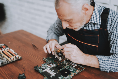 Photo pour Bearded Old Man Repairing Motherboard from PC. Repair Shop. Worker with Tools. Computer Hardware. Magnifying Glass. Soldering Iron. Digital Device. Laptop on Desk. Electronic Devices Concept. - image libre de droit