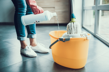 Photo for Woman in Gloves prepearing to Wipe Floor with Mop. Closeup of Girl wearing Protective Gloves mixing Cleaning products with water in Bucket with Mop. Woman Cleaning Apartment - Royalty Free Image