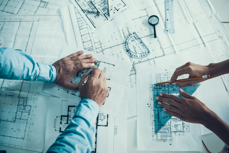 Foto de Closeup of hands of architects Drawing Blueprint. Two Creative Colleagues Designing Plan of new Building Together in Office. Business Corporate People Working Together. Team work Concept - Imagen libre de derechos