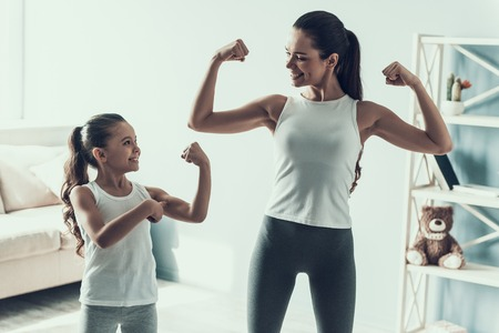 Foto de Young Woman and Little Girl doing Fitness Exercise. Beautiful Young Mother and Adorable Little Daughter during Exercise. Mother and Daughter showing Muscles Together at Home. Healthy Lifestyle - Imagen libre de derechos