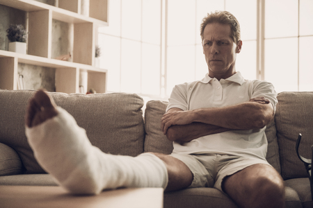 Foto de Man With Fractured Leg Sit On Sofa Crossing Arms. Handsome Caucasian Person Feel Pain in Leg in Plaster Cast Posing with Upset Expression. Rehabilitation and Health Care Concept - Imagen libre de derechos