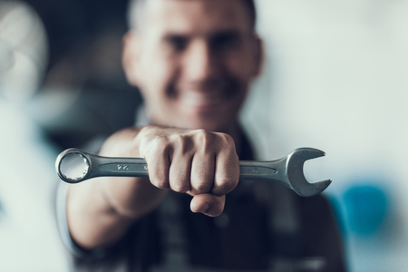 Photo pour Auto Mechanic with Tool on Blurred Background. Close-up of Repairman Strong Fist Holding Metalic Wrench in Garage. Automobile Repair Service Concept. Automobile Master Concept - image libre de droit