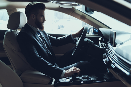 Photo pour Business Man Driving Car Shifting Gear Stick. Stylish Confident Caucasian Person Wearing Black Suit Posing in Auto with Serious Expression. Driving Automobile with Automatic Gears Concept - image libre de droit
