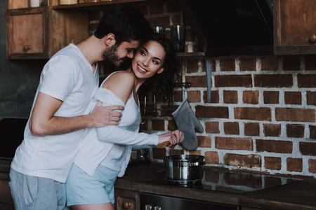 Foto de Young Lovers Smiling and Hugging Before Having Sex. Handsome Couple in Love Hugging in Kitchen. Love Concept. Romantic Date. Relationship. Husband and Wife. - Imagen libre de derechos