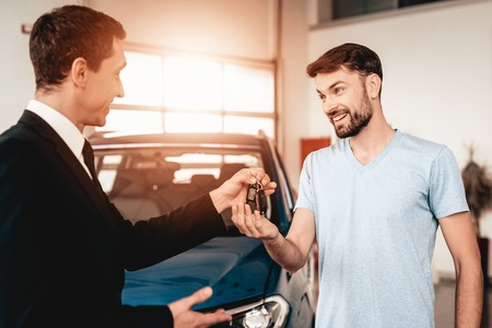 Photo pour Showroom Dealer The Gives Car Keys To The Buyer. Dialogue With A Dealer. Cheerful Customer. Automobile Salon. Make A Decision. End Of A Deal. Good Offer. New Buying. Business Trade. - image libre de droit