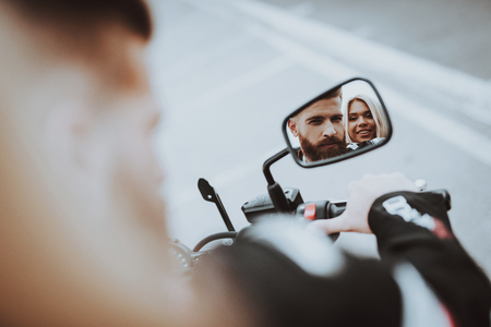 Photo pour Man And Women Stare In A Bike Rearview Mirror. Bikers Concept. Going For Ride. Fashion Riders. Confident Staring. Speed Vehicle. Biker With A Beard. Motorbike Concept. Tripping Together. - image libre de droit