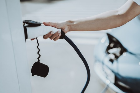 Foto de Car Cable Plug In A Socket. Automobile Charging Station Concept. Innovation Technology. New Generation Electro Hybrid Vehicle Plugin. Ecology Charge Station. Futuristic Power. - Imagen libre de derechos