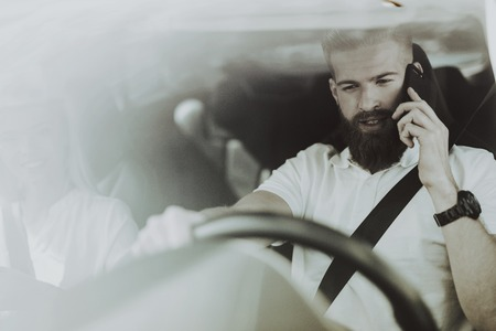 Photo for Man Has A Phone Call Behind The Wheel Of Tesla Car. Innovation Technology. New Generation Electro Hybrid Vehicle. Luxury Design. Futuristic Power. Front Seat. Behind The Glass View. - Royalty Free Image