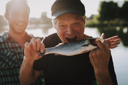 Photo for Old Father with Bearded Son Fishing on River in Summer. Relaxing Outdoor. Bearded Young Man. Men near Lake. Fishing Rod in Hands. Sports in Summer. Weekend on River. Adult Fishermen. - Royalty Free Image