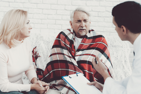 Foto de Young Doctor in Coat Visiting Old Couple at Home. Medical Healthcare Concept. Man in White Coat. Sitting on Sofa. Old Man with Blanket. Grandfather and Grandmother. People with Gray Hair. - Imagen libre de derechos