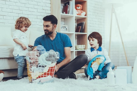 Photo for Two Boys. Help Wash Clothes. Father. Baby with Bright Hair. Smiling Kids. Spends Time. Happy Together. Leisure Time. Man. Smile. Home Time. Family. Holidays. Father Two Boys. Dirty Laundry. Basket. - Royalty Free Image