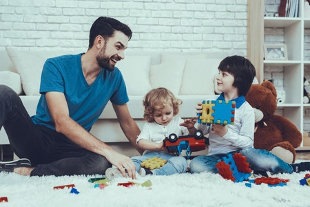 Photo pour Home Time. Happy Together. Smiling Kids. Father. Father Two Boys. Man. Smile. Baby with Bright Hair. Two Boys. Plays Games. Toys. Teddy Bear. Cars. Holidays. Spends Time. Leisure Time. - image libre de droit