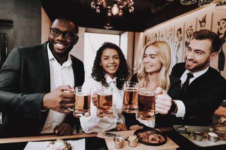 Photo pour Chin-chin. Nightlife. Beer. Two Guys. Girls. Bar. Rest. Drink Alcoholic Beverages. Different Races Communicate. Young People. Have Fun. Together. Clubbing. Joyful. Leisure. Positive. Emotion. - image libre de droit