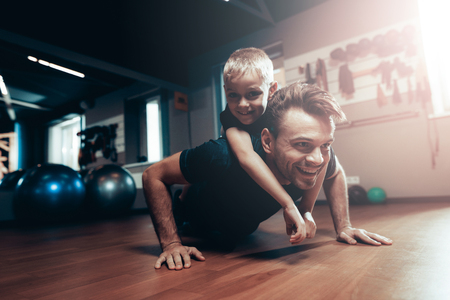 Photo for Man Is Doing Push Ups In Gym With Son On A Back. Parenthood Relationship. Sporty Family Concept. Active Lifestyle. Triceps Exercise. Holiday Leisure. Working Out Together. Fitness Day. - Royalty Free Image