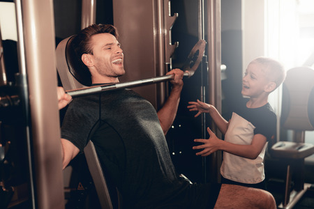 Photo pour Son Support To Father While Lifting The Barbell. Parenthood Relationship. Sporty Family Concept. Active Lifestyle. Happy Childhood. Holiday Leisure. Working Out Together. Fitness Day. - image libre de droit