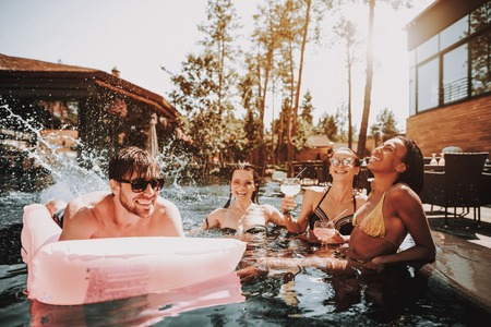 Photo pour Group of Young Happy People Swimming in Pool. Young Smiling Friends wearing Sunglasses Laughing and Relaxing Together in Outdoor Hotel Pool next to Poolside. Summer Vacation Concept. Pool Party - image libre de droit