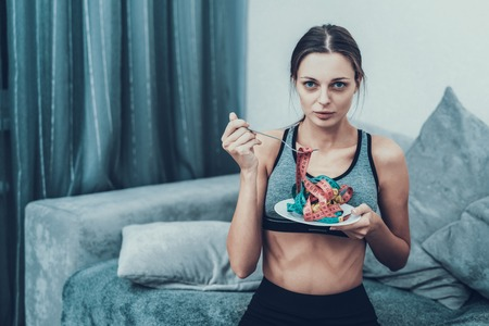 Foto de Young Woman with Tailors centimeter on Plate. Girl with Tailors Centimeter. Diet and Healthcare Concepts. Woman in White Room. Young Girl with Anorexia. Woman in Bra. Girl on Diet. - Imagen libre de derechos
