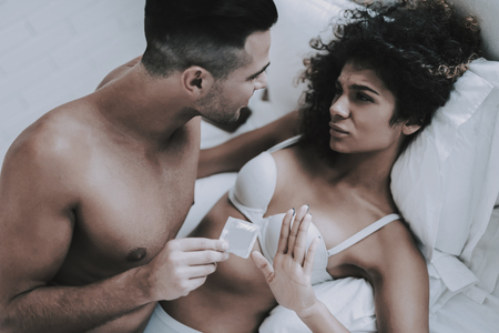 Foto de Young Beautiful Couple in Underwear Lying on Bed. Handsome Man holding Condom. Attractive Woman Refusing Use Contraception. Passionate Romantic Couple about to have Sex at Home. Intimate Relationship - Imagen libre de derechos