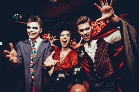 Photo for Young People in Costumes Celebrating Halloween. Group of Young Happy Friends Wearing Halloween Costumes having Fun at Party in Nightclub by doing Scary faces. Celebration of Halloween - Royalty Free Image