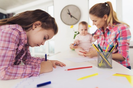 Foto de Happy Family Painting with Pencils Indoors. Cute Pretty Child Drawing on Paper with Colored Pencils at White Table. Young Mom Helping Baby with Pencil. Children Activity Concept - Imagen libre de derechos