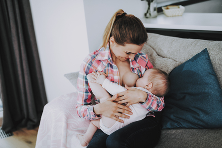 Photo for Young Mothe Breast Feeding Little Baby Indoors. Portrait of Happy ?aucasian mother Sitting on Couch in Living Room and Holding Cute Adorable Child on Knees. Parenthood and Childhood Concept - Royalty Free Image