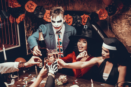 Photo for Young Smiling People in Costumes Clinking Glasses. Group of Young Happy People Wearing Costumes at Halloween Party Sitting at Table and Drinking Champagne. Celebration of Halloween - Royalty Free Image