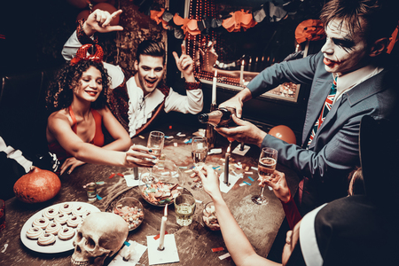 Photo pour Young People Wearing Costumes Drinking Champagne. Group of Young Happy People in Costumes at Halloween Party Sitting at Table and Drinking Champagne. Young Man Pouring Champagne - image libre de droit