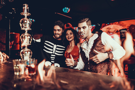 Photo for People in Costumes Looking at Flaming Cocktail. Group of Smiling Young Friends Wearing Costumes Excited about Flaming Cocktails on Bar counter in Nightclub. Celebration of Halloween - Royalty Free Image