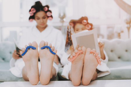 Foto de Spa Day in Beauty Salon. Little Lady with Curlers. Mother and Daughter in Spa. Consept Beauty Salon. Beautiful Face. Woman and Happy Child. Woman with Curlers. Doing Selfie. Blue Sofa in Spa Salon. - Imagen libre de derechos