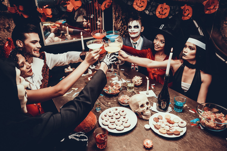 Photo for Young Smiling People in Costumes Clinking Glasses. Group of Young Happy People Wearing Costumes at Halloween Party Sitting at Table and Drinking Cocktails. Celebration of Halloween - Royalty Free Image