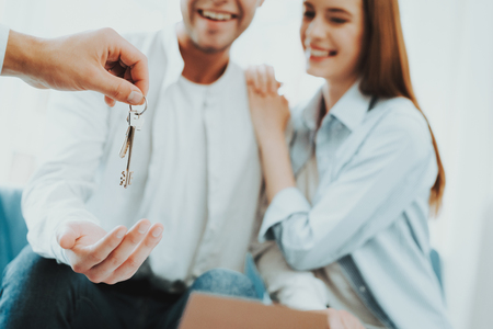Photo pour Young Couple Stare On The Key In Rieltors Hands. Bright Office. Keys In A Hand. Buying A Property. Panoramic Windows. Business Meeting. Customer And Buyer. Offer Discussion. Professional Agreement. - image libre de droit