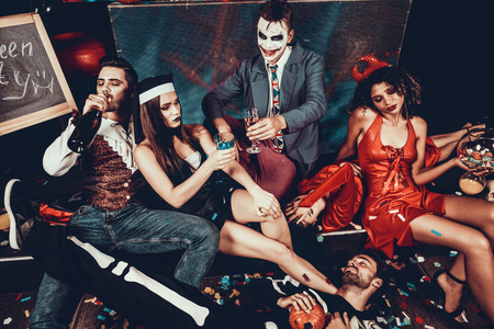 Foto de Drunk Young People in Costumes Resting after Party. Group of Young Friends Wearing Costumes Resting after Halloween Party by lying on Floor of Nightclub and Drinking. Nightlife Concept - Imagen libre de derechos