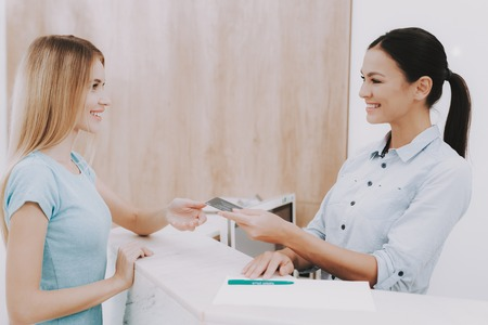 Photo pour Woman Receptionist. Business Card in Salon. Workplace in Beauty Salon. White Interior. White Reception Desk. Beauty Consept. Smiling Salon Employee. Customer Registration. Employee Talking Client. - image libre de droit