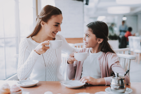 Photo pour Mother and Daughter. Leisure Time. Tea Party. Smiling People. Love. Drink Tea. Have Fun. Enjoyment. Bonding. Together in Cafe. Cheerful Girls. Happy Together. Good Relationship. Happy Holidays. - image libre de droit