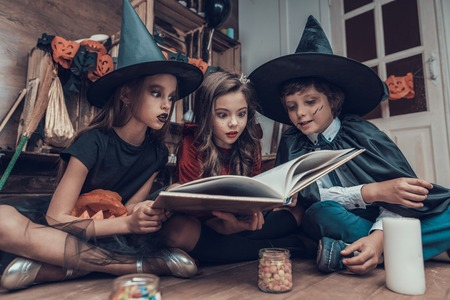 Foto de Little Children in Halloween Costumes Reading Book. Cute Smiling Kids wearing Scary Halloween Costumes Sitting on Floor next to Jars full of Candys and Candles. Celebration of Halloween - Imagen libre de derechos