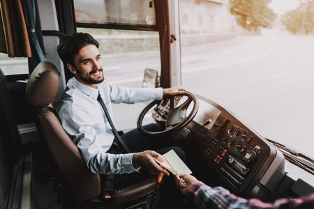 Photo pour Smiling Young Driver taking Ticket from Passenger. Handsome Happy Man wearing Blue Shirt Sitting on Driver Seat of Tour Bus. Attractive Confident Man at Work. Traveling, Transport and Tourism Concept - image libre de droit