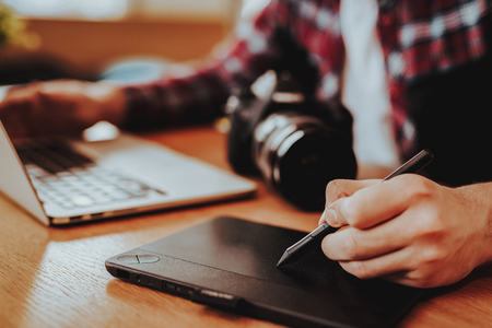Foto für Closeup of Male Graphic Designer Hands Working. Guy Sitting at Table Using Digital Tablet with Stylus Pen, Laptop Keyboard and Camera Indoors. Freelancing and Distance Job Concept - Lizenzfreies Bild