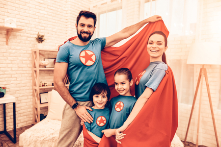 Photo pour Portrait of Cute Smiling Super Hero Family at Home. Smiling Parents with Children Sitting on Sofa at Home. - image libre de droit