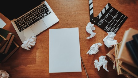 Foto de Top View of Text Writer Stuff on Workplace. Closeup of Wooden Desktop with Laptop, Crumpled Paper Sheets, Stacks of Books and Movie Clapper Board. Journalism and Screenwriter Concept - Imagen libre de derechos