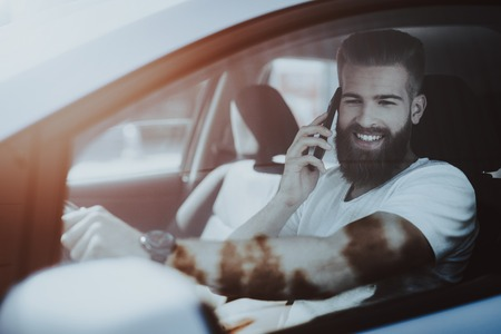 Photo for Man Has A Phone Call Behind The Wheel Of Car. Innovation Technology. New Generation Electro Hybrid Vehicle. Luxury Design. Futuristic Power. Front Seat. Behind The Glass View. - Royalty Free Image