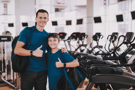Foto per Young Father and Son near Treadmills in Modern Gym. Healthy Lifestyle Concept. Sport and Training Concepts. Modern Sport Club. Sport Equipment. Family Sport. Running Tracks. Parent with Child. - Immagine Royalty Free