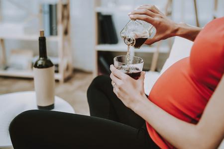 Foto de Woman is Pouring Whiskey from Bottle to Glass Cup. - Imagen libre de derechos